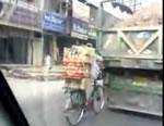 ダンプに掴まって自転車で荷物運び