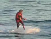 サメに餌をくわえさせてサーフィン