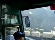 崖の上の山道で何度も切り返すバスに乗客は不安顔