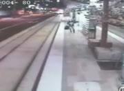路面電車の線路に転落した酔っぱらいを救出する警官