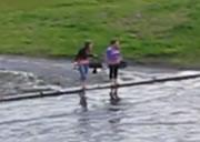 大雨による道に溢れた水で横切れない女性二人を助ける男