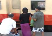 通過する列車に無理して乗り込む男女