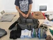 大量の衣類をバッグに詰める