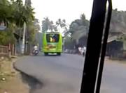 カーブで片輪を上げて走るバス