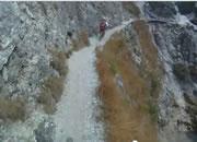 細い崖路を自転車で走行