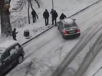雪道で滑り落ちる車を止める男