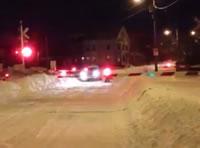 線路に雪が積もった踏切を電車が通過
